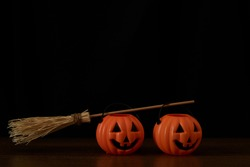 Two pumpkins and a witch broom on black background. Happu halloween