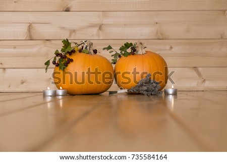 Two pumpkins in wooden log cabin with negative space for text