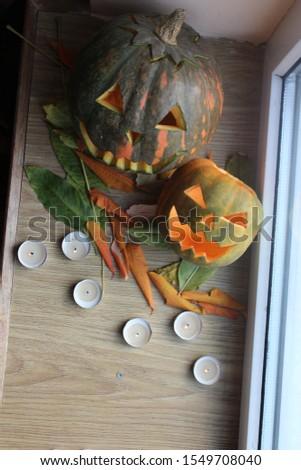 two pumpkins on a windowsill for Halloween