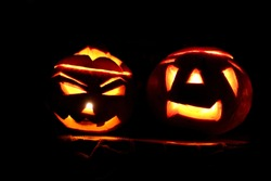 Two Pumpkins Turned into monstrous candle or jack lanterns for Halloween party