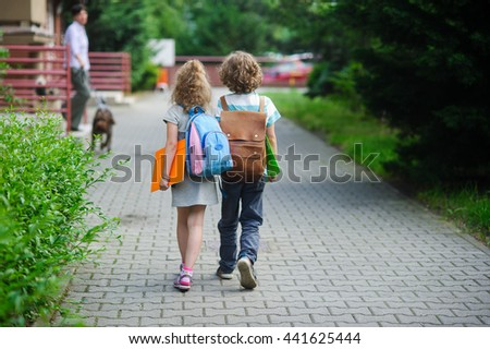 Two pupils of primary school go hand in hand. Boy and girl with school bags behind the back. Beginning of school lessons. Warm day of fall. Back to school.  Little first graders.