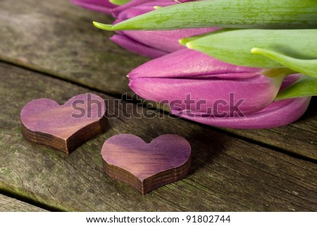 Two purple hearts and tulips on a wooden table