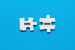 Two puzzle pieces with the word win. Win win situation in business strategy or successful deals concept.