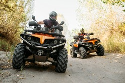 Two quad bike riders travels in forest, front view