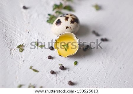 Two quail eggs on white wooden table
