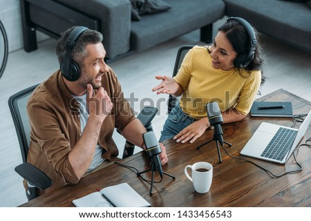 two radio hosts talking and smiling while sitting near microphones in broadcasting studio