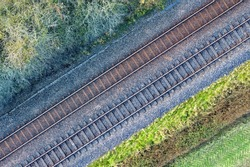 Two railway tracks which consists of two parallel steel rails, anchored perpendicular to members called ties (sleepers) of concrete to maintain a consistent distance apart, or rail gauge. With trees.