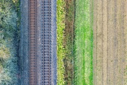 Two railway tracks which consists of two parallel steel rails, anchored perpendicular to members called ties (sleepers) of concrete to maintain a consistent distance apart. Line pattern. Copy space.