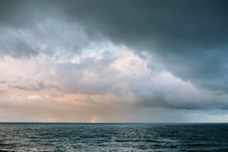 Two rainbows at the horizon over stormy Pacific Ocean with heavy dark gray storm clouds off Hawaii