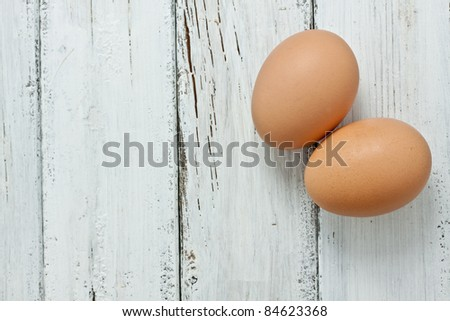 two raw eggs on a wood table