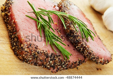 Two raw, eye of round, Alberta beef steaks, with pepper & spices and topped with fresh rosemary.