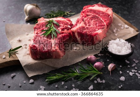 Two raw fresh marbled meat black angus steak ribeye, garlic, salt and  on dark background #366864635