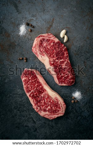 Two raw, fresh Wagyu marbled beef steaks, strip loin on a dark stone background, top view