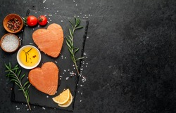 Two raw salmon fillets with heart shaped spices on a stone background with copy space for your text