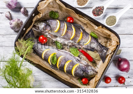 two raw trouts fish on the baking dish with cherry tomatoes, fennel, garlic, onion and spices, view from above