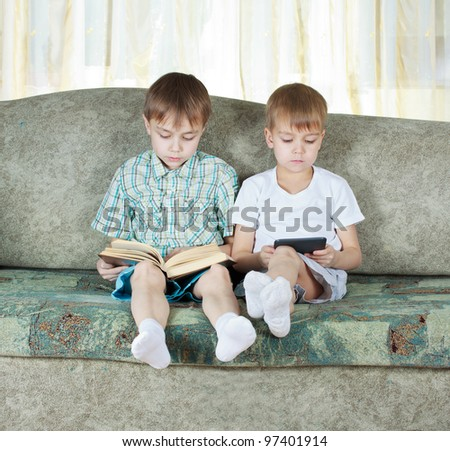 Two reading boys at sofa. One with paper book, other with electronic book