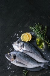 Two ready to cook raw bream fish with herbs, lemon and olive oil on stone slate board over black textured background. With copy space. Top view