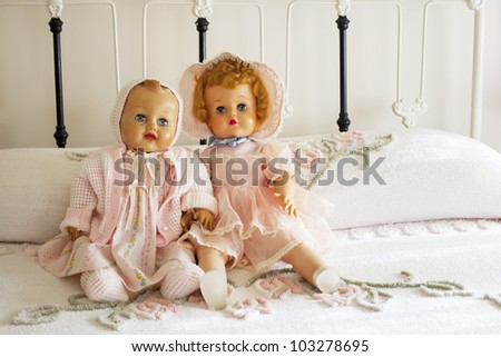 Two real looking antique baby dolls dressed in vintage pink outfits sitting on vintage chanille bedspread on antique iron bed.