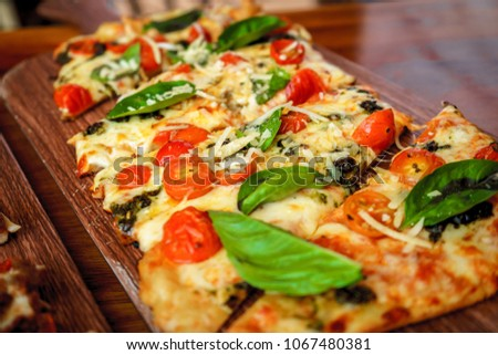 Two rectangular pizza on a wooden table in an Italian restaurant.