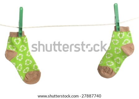 Two recycle print child socks hang on clothesline, environmental energy conservation theme