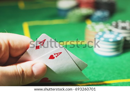 Two red aces in hand. Green poker table with chips blurred on background