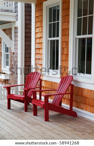 Two red Adirondack chairs on a wood deck against a brown wood shake home