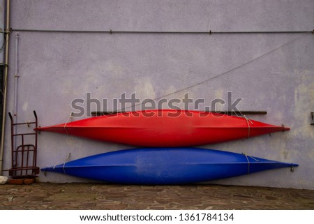 Two red and blue canoes resting on the wall, ready for the first exit into the sea. Open canoes ideal for recreational activities, sports, water tourism. #1361784134