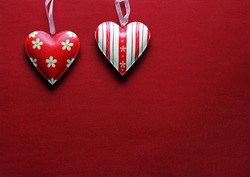 Two red and white metal hearts on a red paper background