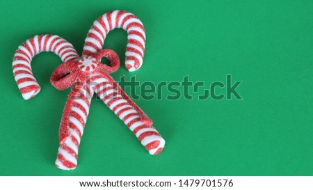 two red and white striped candy canes with candy and a bow laying flat on a green festive background with copy space #1479701576