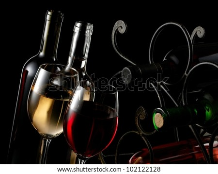 Two red and white wine glasses with bottles and wrought iron rack - stock photo