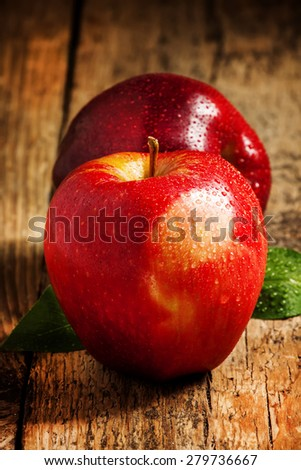 Two red apples with water drops on a wooden table, selective focus