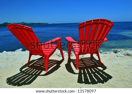 two red beach chairs on white sand with caribbean sea view