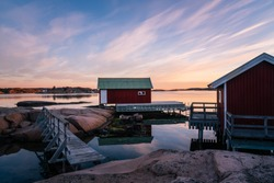 Two red boat houses with a small wooden bridge at sun rise in the Swedish archipelago on the west coast in Hunnebostrand. Bohuslän