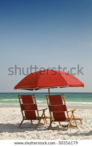 Two red canvas lounge chairs and umbrella on a beautiful beach facing the ocean