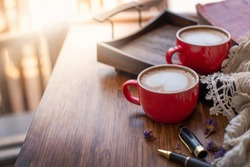 Two red coffee cups on a wooden tray has a scarf, and a pen on the wood table
