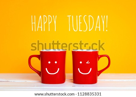 Two red coffee mugs with a smiling faces on a yellow background with phrase Happy tuesday. Happy coffee mugs. #1128835331