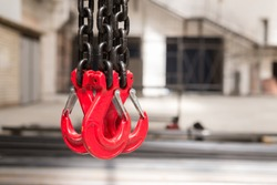Two red crane hooks on a thick chain inside the factory floor