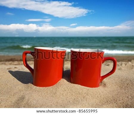 two red cups on a sunny beach