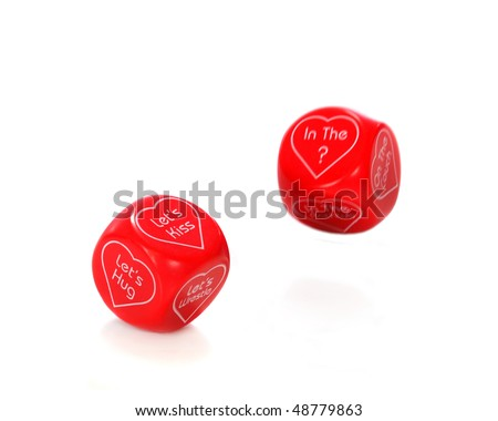 Two red dice with things to do and where to do it enclosed in heart shapes.  Isolated on white.  Motion blur on second dice.