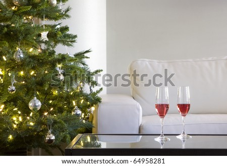 two red drinks by christmas tree in modern white living room