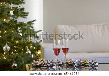 two red drinks by christmas tree with lights, bows in modern living room - stock photo