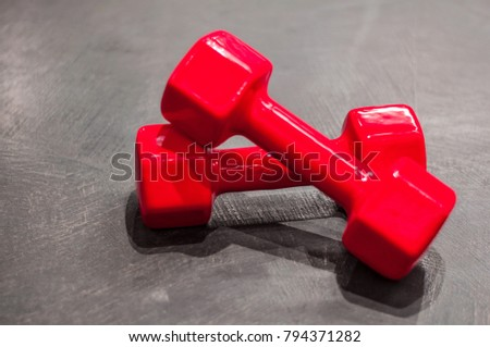 Two red dumbbells lie crosswise on the gray floor in the right part of the photo #794371282