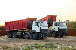 Two red dump trucks simultaneously lifted the bodies to unload the sand. Cargo transportation services. Large multi-ton truck. Unloading cargo. Construction site and machinery. Banner. Common view.