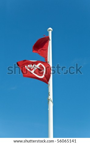 Two red flags on a flagpole at a Gulf Coast Beach mean no swimming or fishing due to dangerous surf, storms, or toxic water conditions.