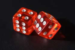 Two red glass dice on a dark leather background. The result is four and six or five. Two red dice on a dark textured background, macro photography.