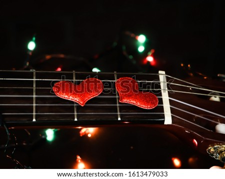 Two red glitter hearts  on acoustic guitar strings with string lights background , Valentine's day concept