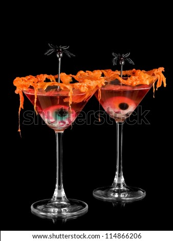 Two red halloween cocktails with eyes and spiders