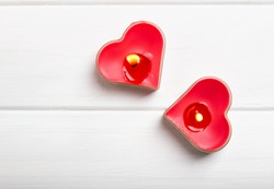 Two red heart shaped candles on the white table, top view