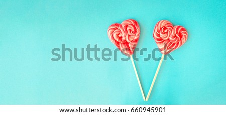 Two red heart shaped lollipops on a vibrant blue background with copy space on left for Valentines card. Valentines Day background #660945901