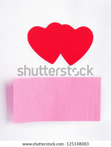 Two red hearts and a sticky-note stuck on paper sheet